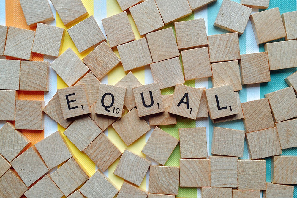 "A photo shows Scrabble game tiles spelling out the word ""equal."""
