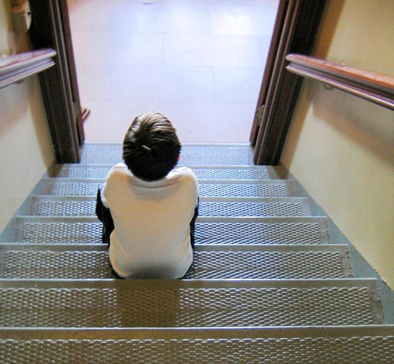 A child is shown from behind sitting on metal stairs looking into a room.