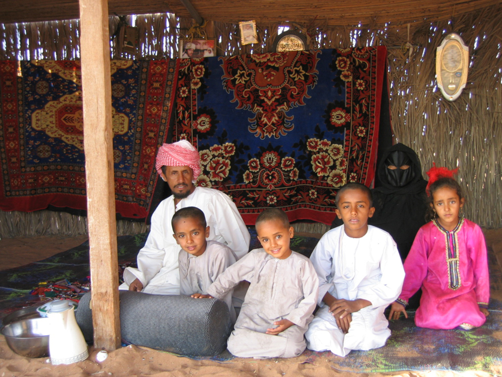 A man in a turban, a woman in a veil covering her face, and four children are shown sitting in a thatched hut. Carpets can be seen on the sandy ground and on the walls of the hut.