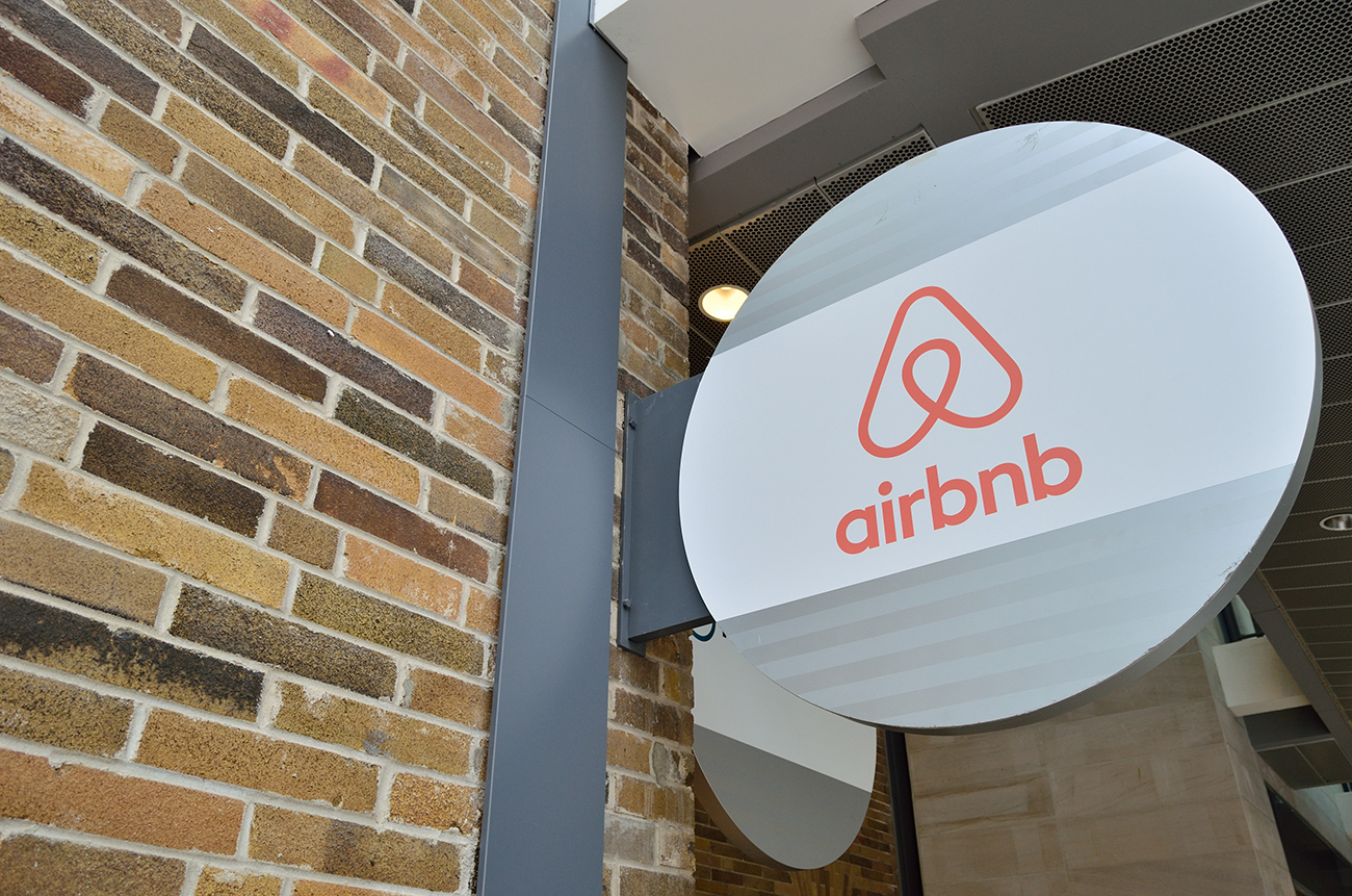"A photo shows the signature and logo of ""Airbnb"" company at the entrance of an apartment building."