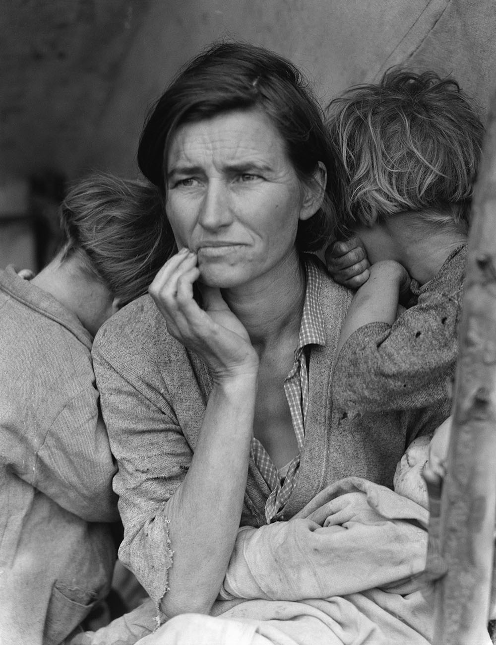 A black and white photo shows a desperate-looking woman sitting with two children who bury their faces against her shoulders.