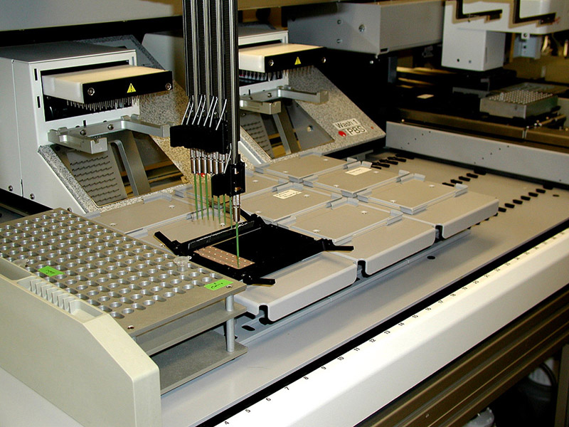 Photo shows a protein pattern analyzer. It is a large piece of equipment on a desktop with pipettes at the end of long steel tubes.