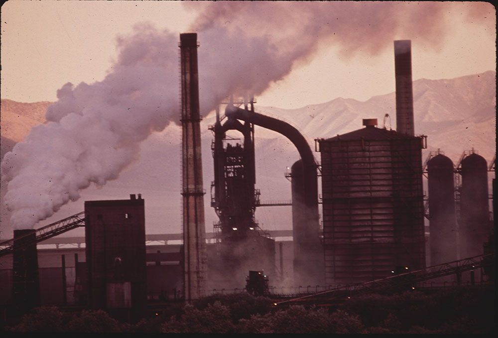 A photograph of an old steel mill at sunrise with smoke rising out of a smoke stack.