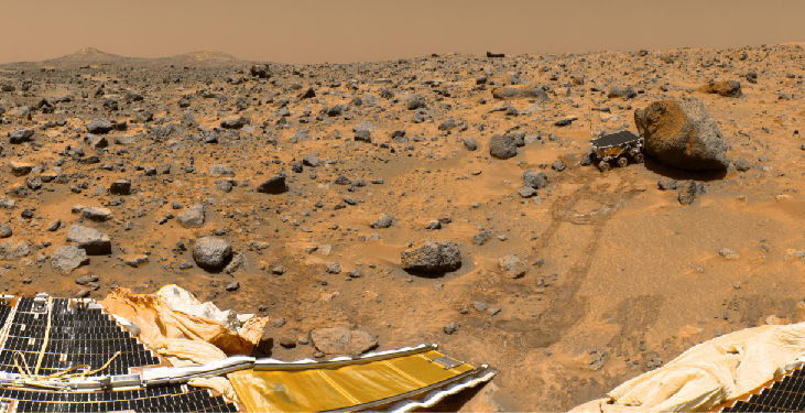 Surface view from Mars Pathfinder. At the lower left in this image, a portion of the lander and the ramp used to deploy the Sojourner rover is seen. Tracks lead away from the ramp to the large boulder at the upper right of this image. The rover is positioned immediately to the left of the boulder.