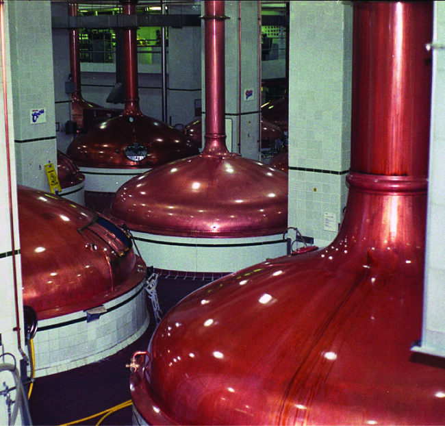 A picture is shown of four copper-colored industrial containers with a large pipe connecting to the top of each one.