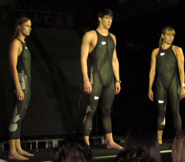 Three swimmers with are each wearing an L Z R Racer Suit, which is a swimsuit composed of elastane nylon and polyurethane. The seams of the suit are ultrasonically welded to reduce drag.