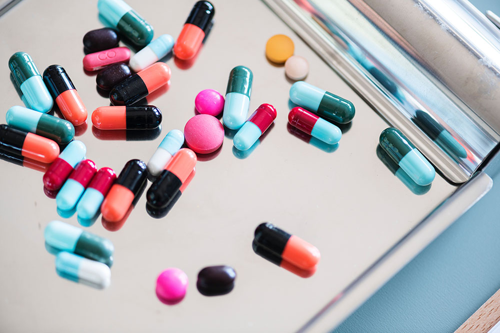 A photo shows assorted pills on a metal tray.
