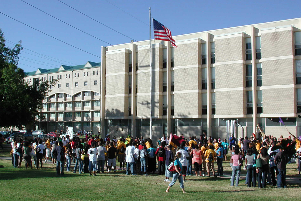 Students standing on the grounds of a high school or college campus.