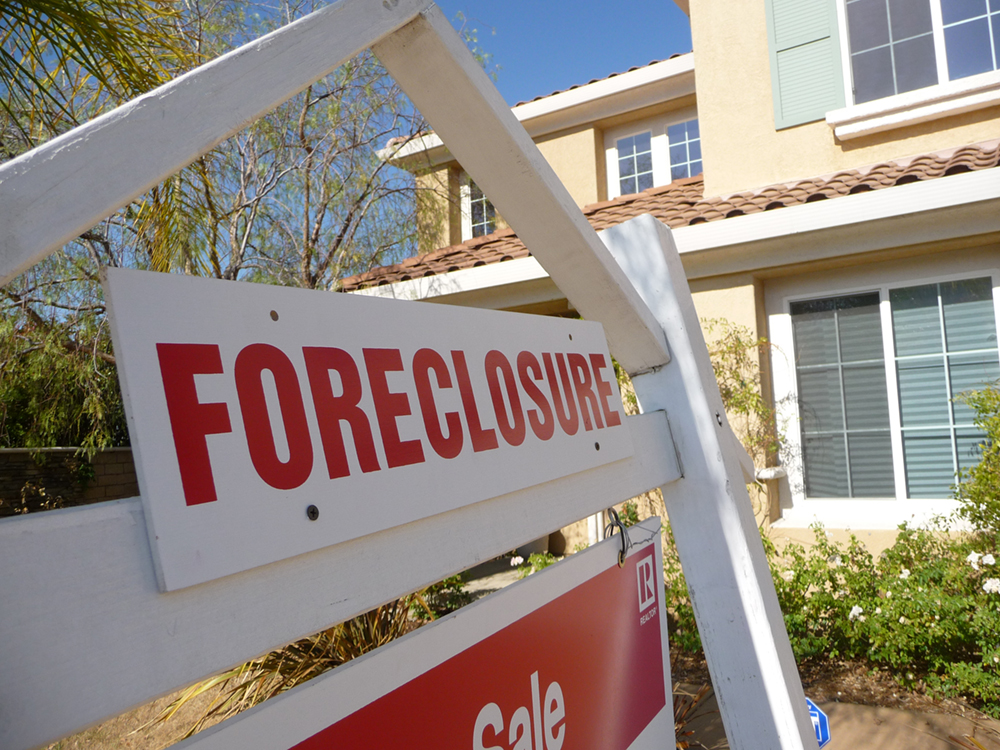 A house with a foreclosure sign in front of it.