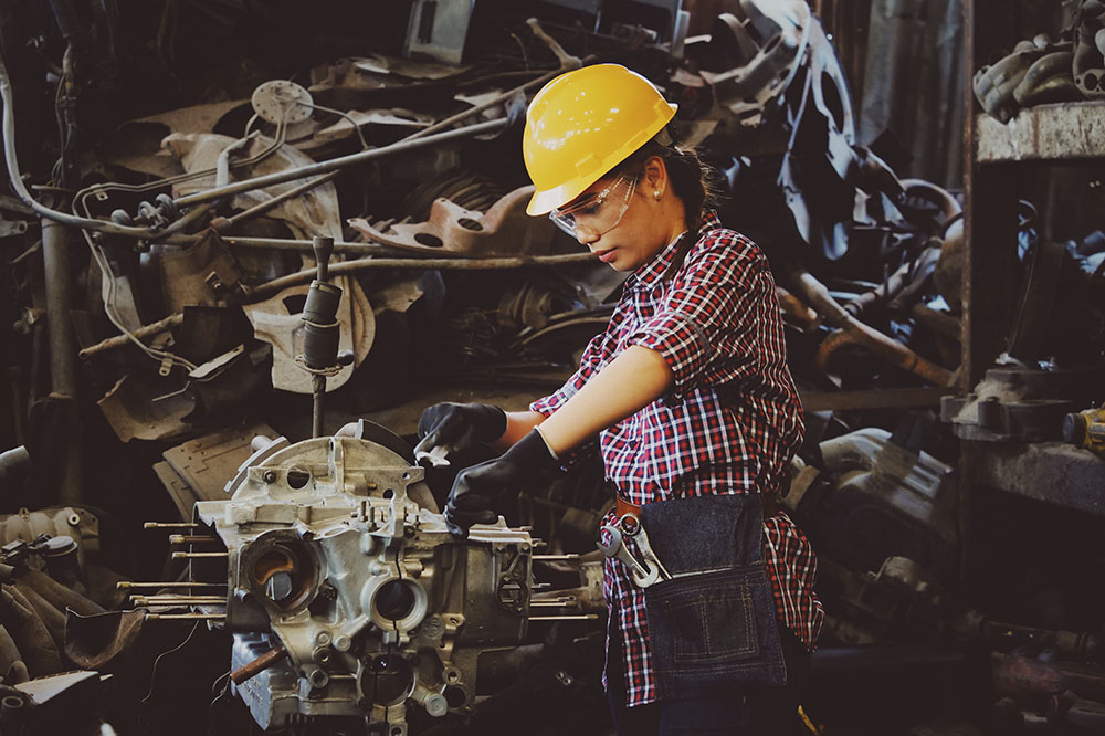 A photo shows a woman wearing safety gear and working on a car part in a factory.