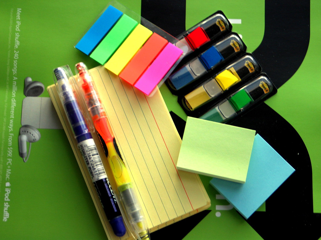 A photo shot directly from the above shows a set of stationery items including, papers, highlighters, pens, and sticky labels.