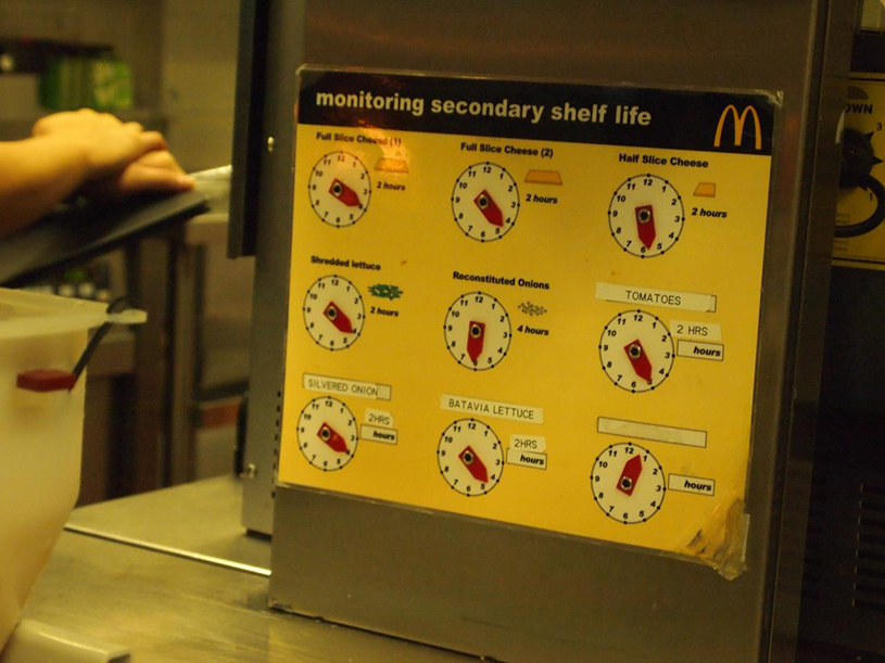 "A photo shows a leaflet titled ""Monitoring secondary shelf life"" affixed on the kitchen wall of a McDonald's store. It reports the secondary shelf-lives for six different ingredients."
