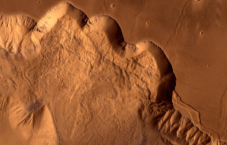 Erosion on Mars. The sloped valley wall winds its way across this image from the upper left section to lower right section while separating the flat plains above and the debris covered valley floor below.