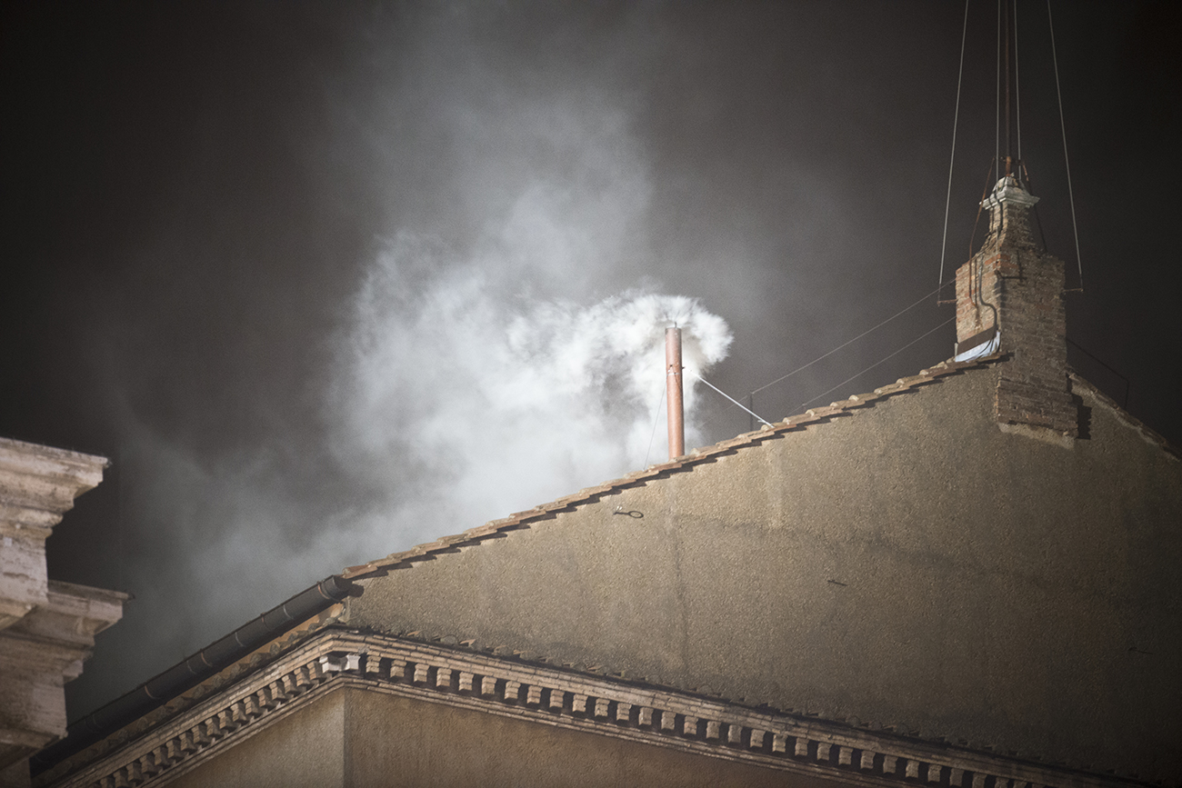A photo shows white smoke rising from the chimney of the Sistine Chapel in Vatican City.