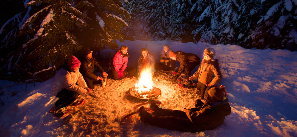 Photograph of people sitting around a campfire in the snow.