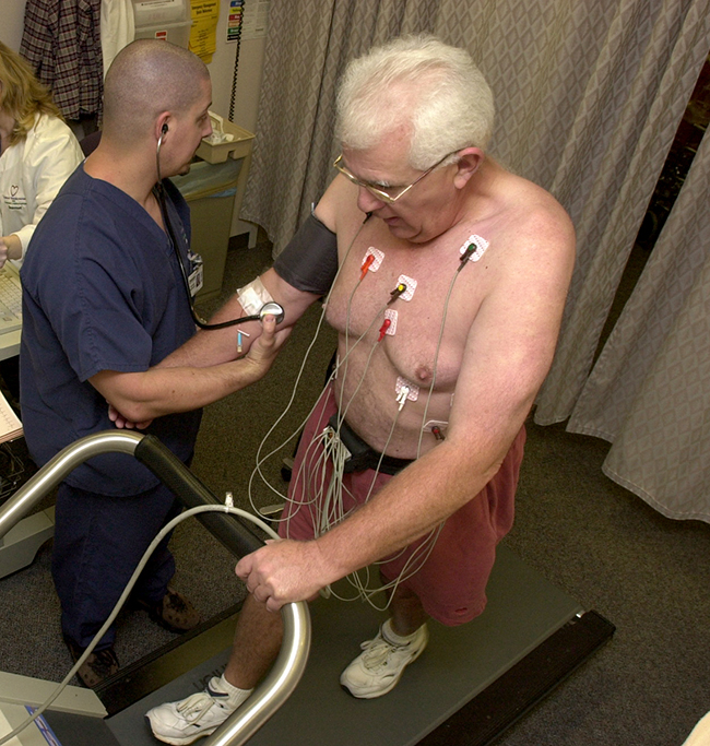 A photo is shown of two men, one walking on a treadmill with various wires connected to his torso region, and the other collecting blood pressure data from the first man.