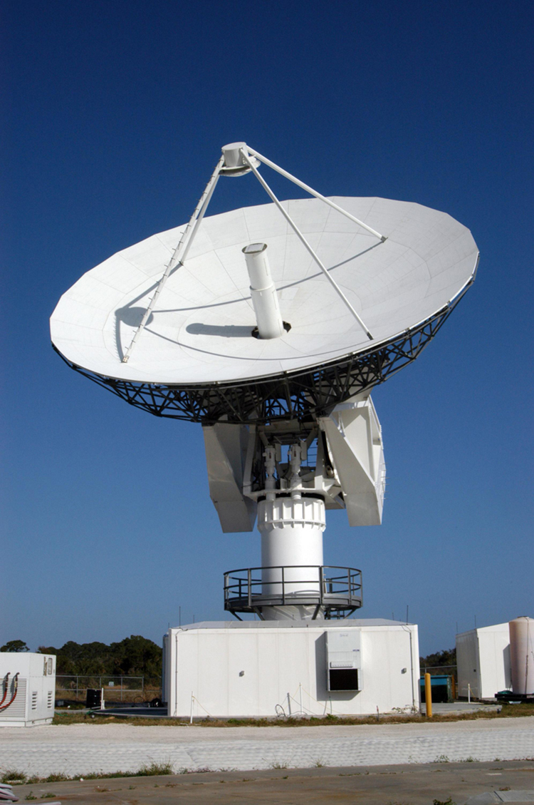 The large, round dish antenna looking like a giant white saucer is shown. It rests on a pillar shaped structure with a moveable tracking system that allows it to point towards a target object, send out electromagnetic waves, and collect any signals that bounce back from the target object.