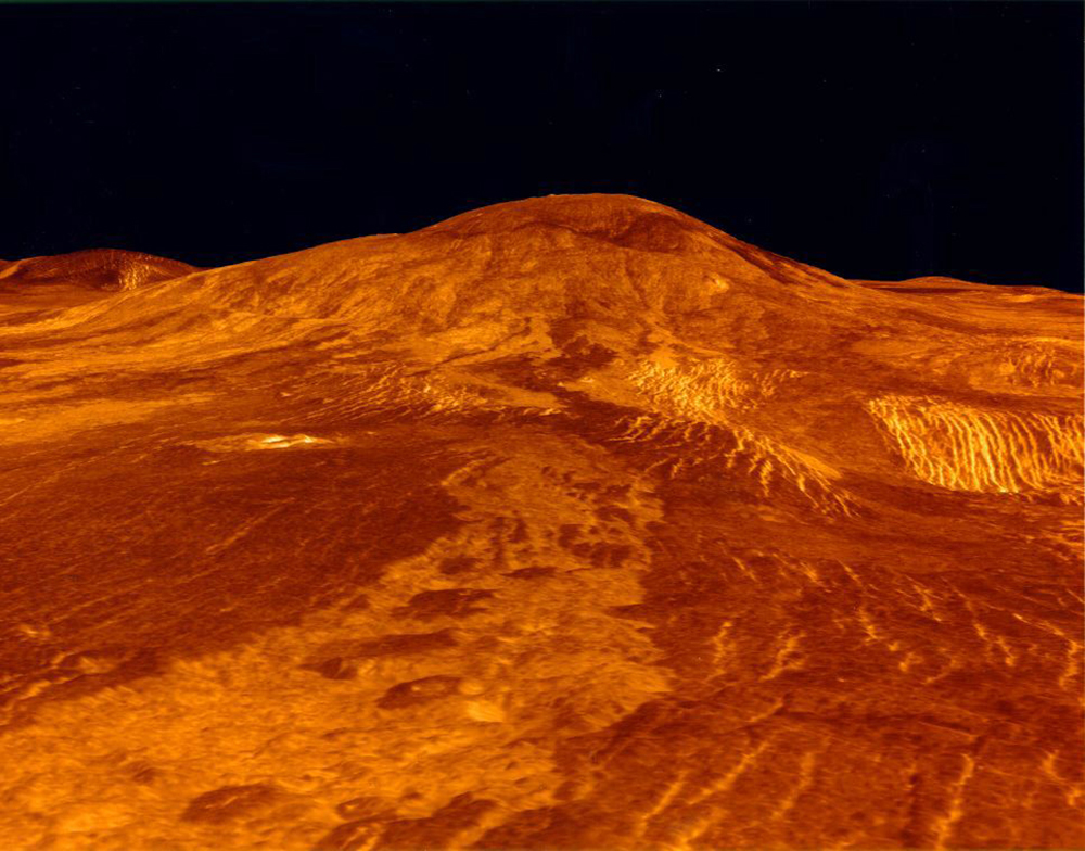 A photograph of the surface of planet Venus is shown. The lava flows on Venus are shown as orange red color of the surface.