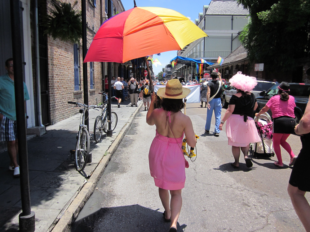 A woman walking down the street with a rainbow umbrella is shown here.