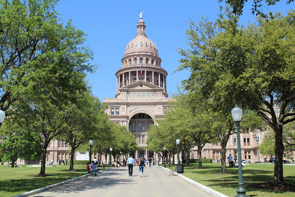 A photo shows the State of Texas Capitol Building with people walking toward the building during the daytime.