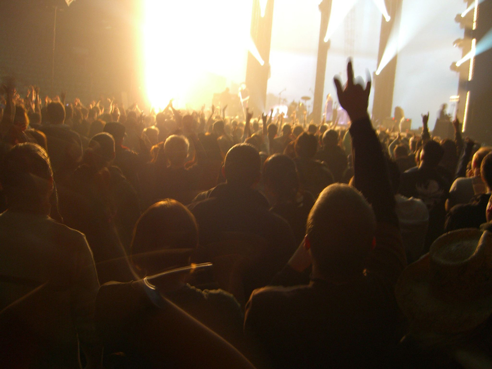 A crowd of people at a concert is shown from behind. Multiple lighting effects can be seen emanating from the stage.