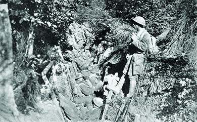 A photograph shows several U.S. soldiers sitting and standing in a trench.
