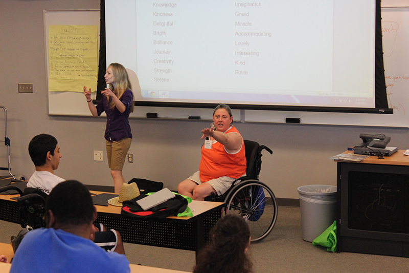 A photo shows a woman lecturing disabled students in a lecture hall, with a large projector screen in the background. Another woman in wheelchair appears by her side trying to interact with the students.
