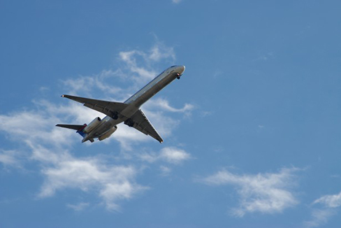 A photograph of an airplane flying in an upward direction is shown. The sky is partly cloudy.