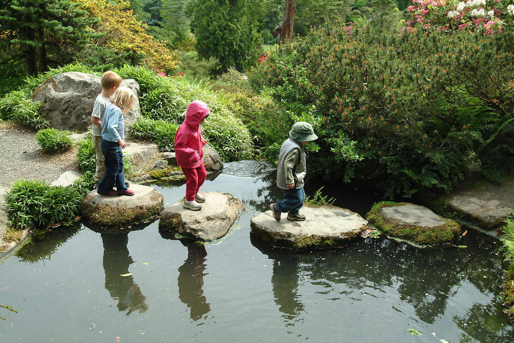 Four children are shown crossing a stream by walking on stones.
