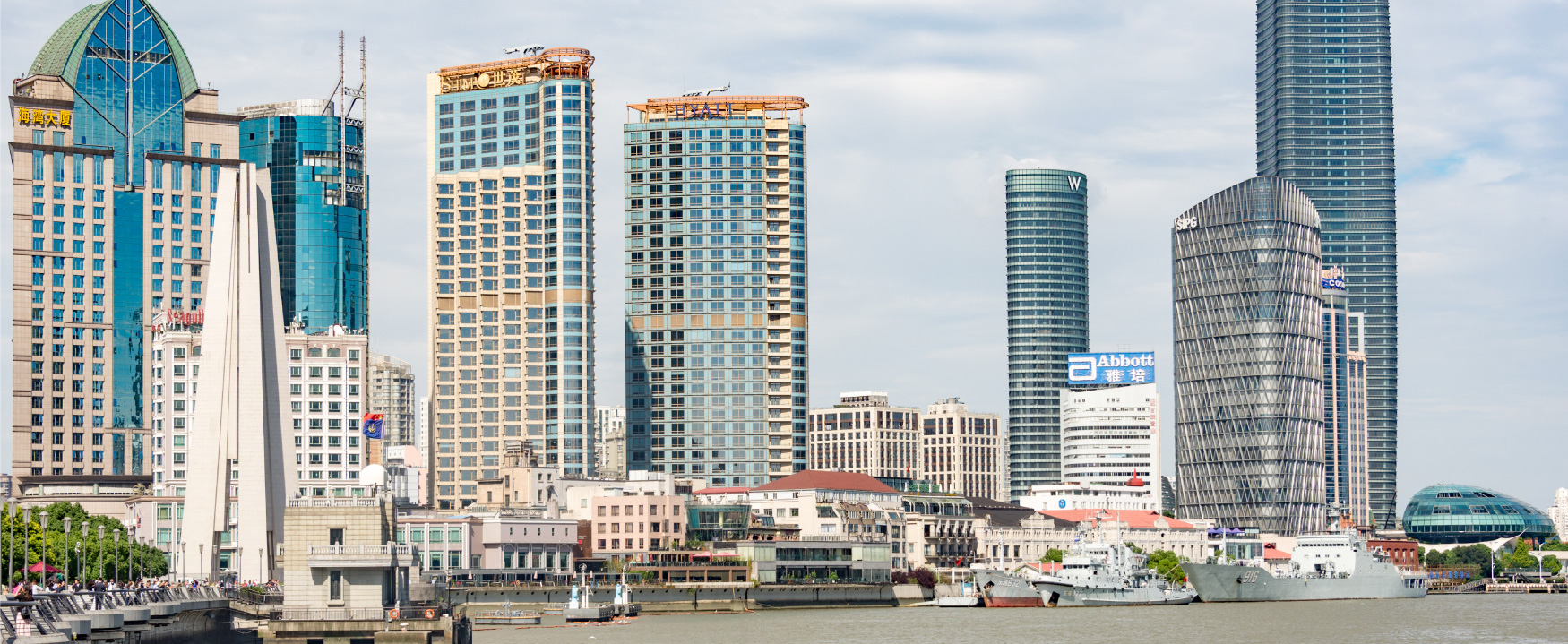 A photograph shows a port city skyline, where the buildings all appear to be very new, and very sleek.