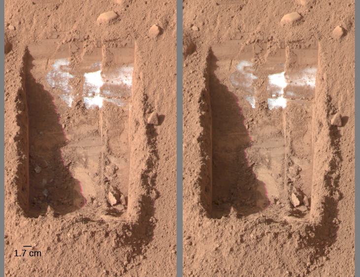 "Evaporating ice on Mars. This image has two panels, and each of them show the same little ""trench"" excavated by the Phoenix lander. On the left, in the lower left portion of the rectangular trench, three gray spots can be discerned. The scale at lower left reads 1.7 c m. In the right hand image, taken four days later, the three spots have vanished."