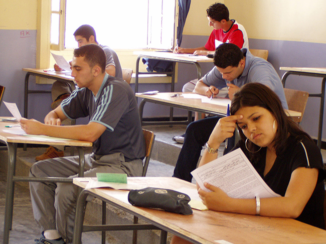 A photo shows students writing exam in an examination hall.
