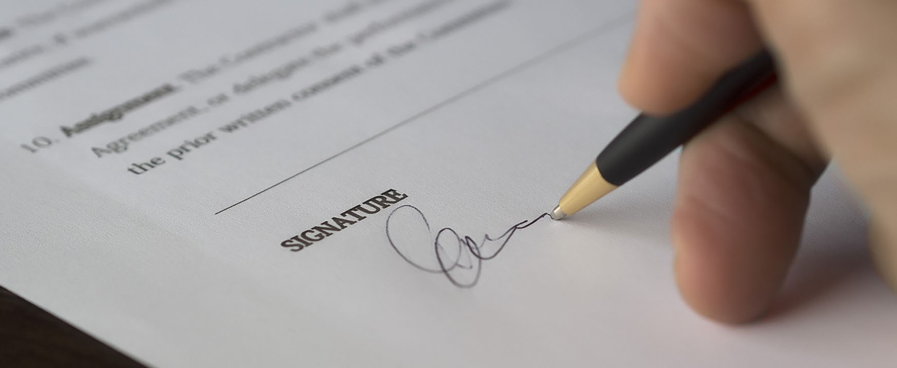 A close up of a signature line on a contract, with a person's hand signing it.