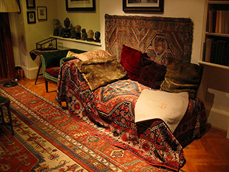 This photograph shows what Freud's famous psychoanalytic couch looked like. The couch is draped in tapestries and pillows, and the room is decorated with sculptures, books and pictures on the wall.