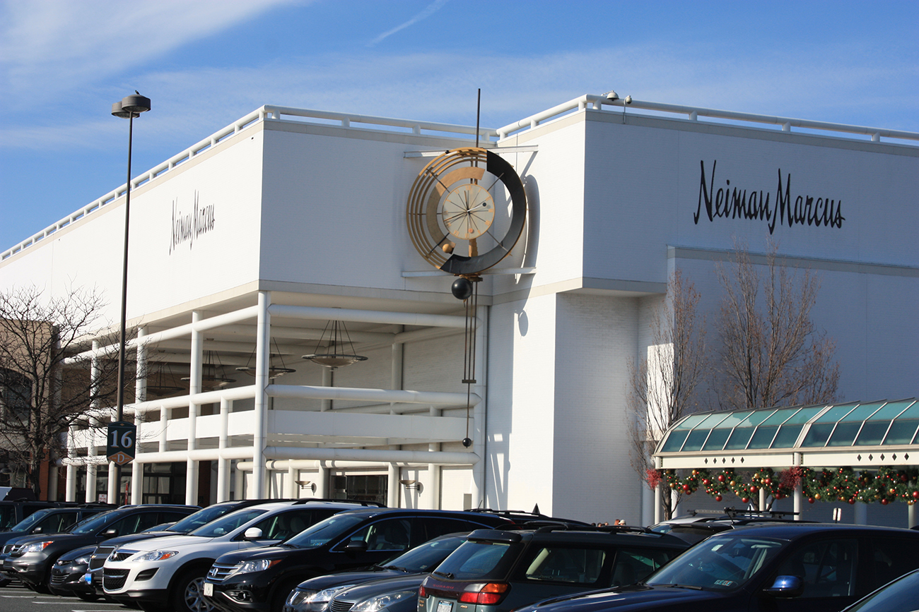 A photograph shows the outside of a Neiman Marcus store. It is a large building with a large metal clock statue, and covered walkway decorated with Christmas decorations.