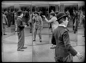 This black-and-white still shot shows Charlie Chaplin and a thief in a maze of mirrors. Images of Chaplin and the thief appear in mirrors, within mirrors, within mirrors.