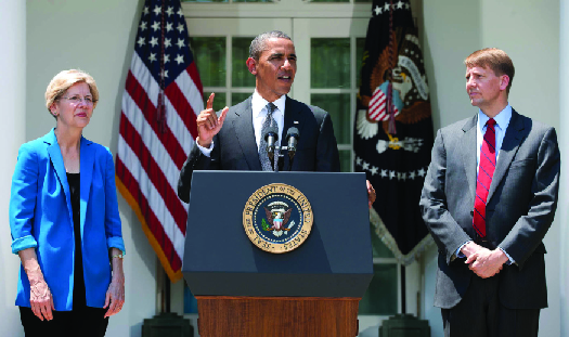A photo of President Barack Obama speaking at a podium with Elizabeth Warren to his left and Richard Cordray to his right.