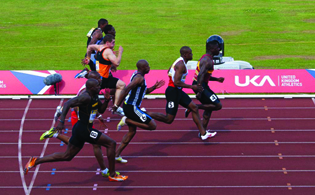 A photograph of 8 male runners in a track race.