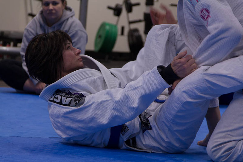 A photo shows two persons in jiu-jitsu uniforms sparring during a jiu-jitsu training session as another woman in the background watches them.