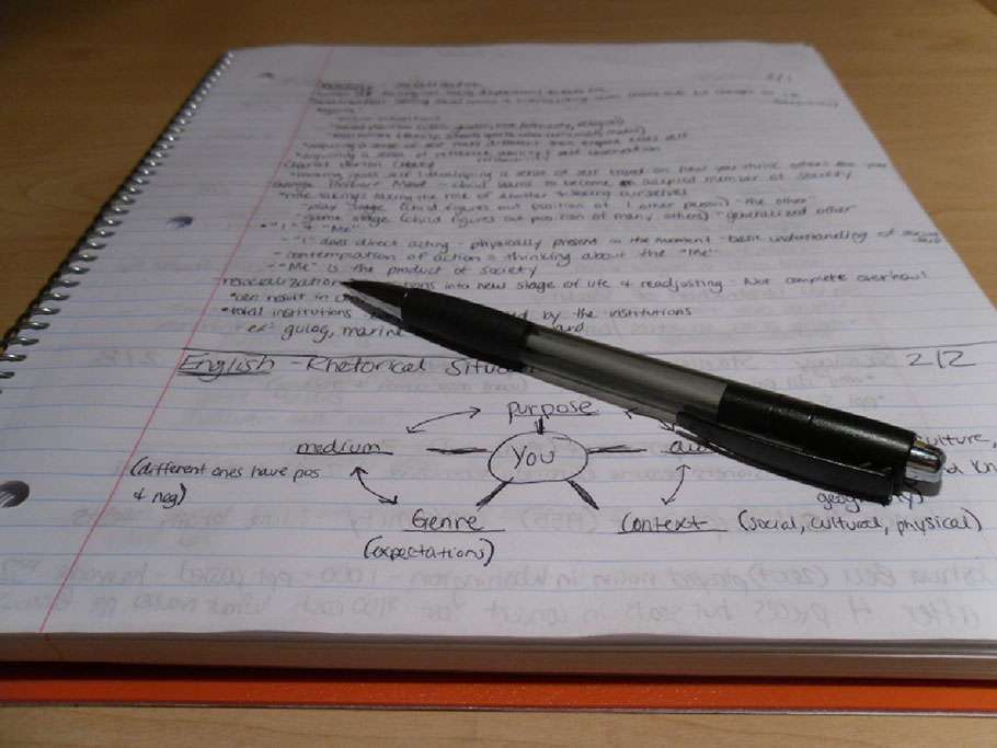 A pen placed atop a student's notebook, with the page full of handwritten notes and a diagram.