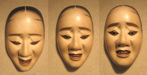 Three masks are arranged side by side. The masks are almost identical, but with slightly different facial expressions resulting from the masks being at different angles. The first mask is tilted downward and has downcast eyes. The second mask is shown straight on and is directing its gaze slightly higher than the first. The third mask is tilted upwards so its gaze is directed more upward.