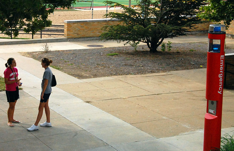 A photo shows two female college students talking to each other on a college campus. A large emergency phone with buttons and siren appears toward the right.