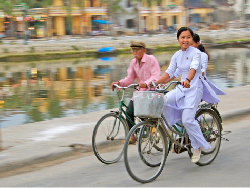 Picture shows three people riding bicycles next to a canal.