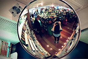 The image shows a woman taking a picture in front of a convex mirror.