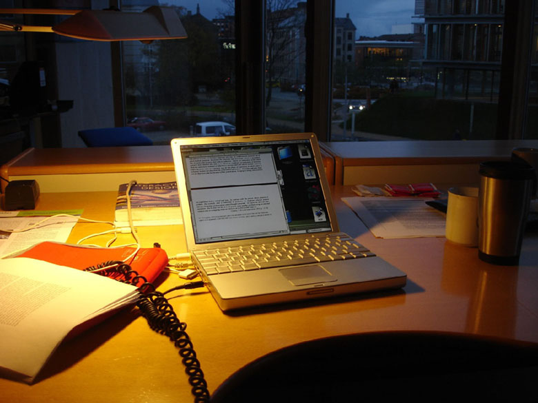 A laptop sits on a work table displaying a word document.