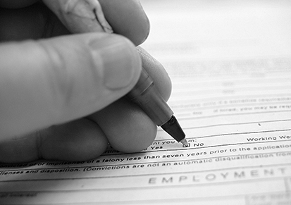 A photo of a person's hand filling in a survey check box labeled 'No' with a pen.