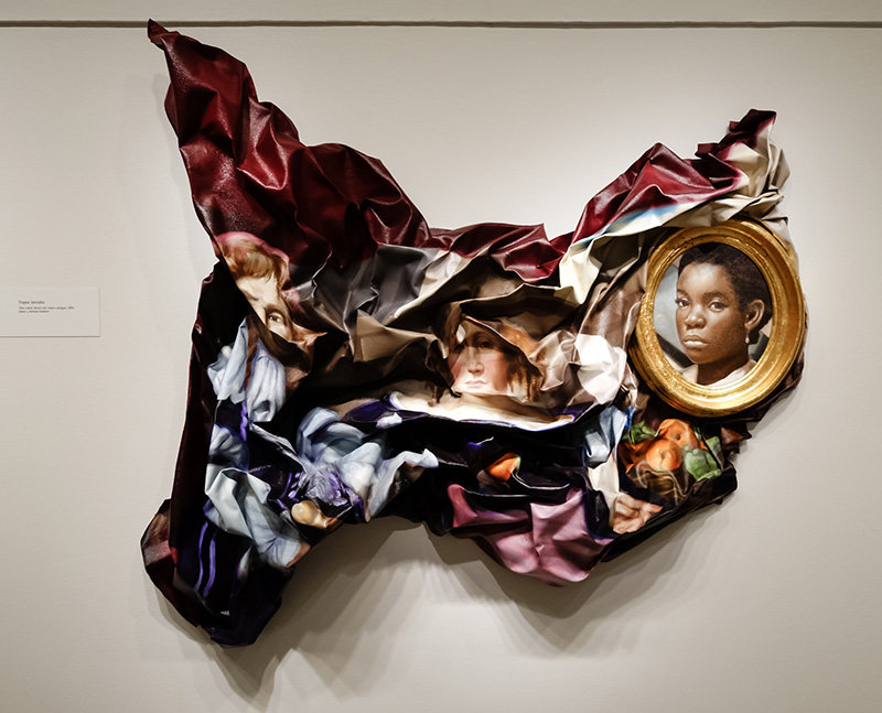 "A photo shows the famous work ""Twisted Tropes"" by Titus Kaphar hanging on a wall."
