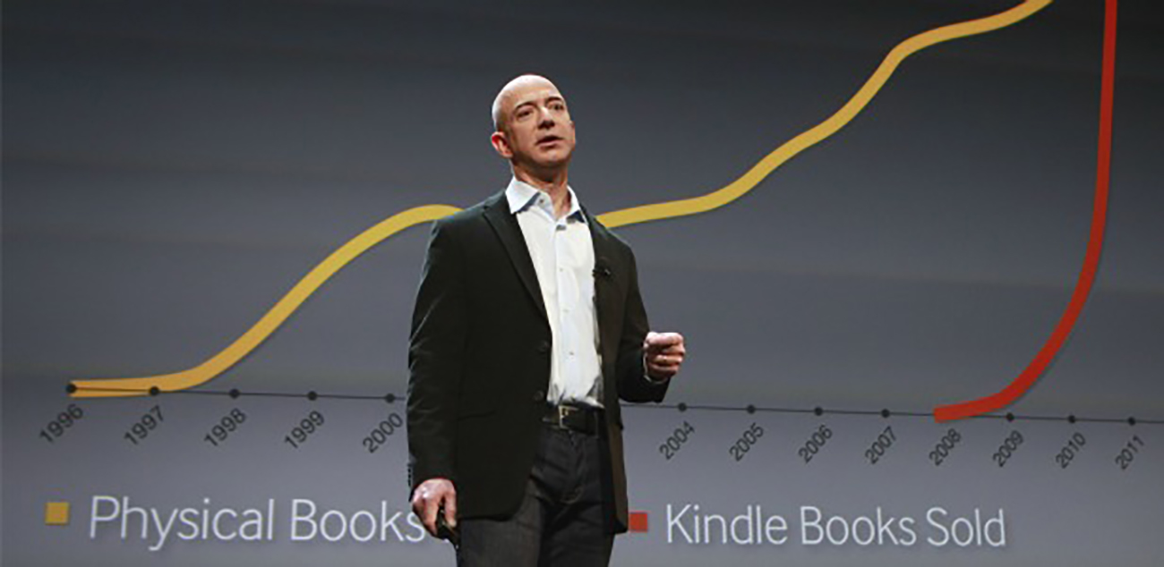 A photo shows Jeff Bezos flashing the slide showing the phenomenal growth of Amazon's Kindle eBook sales in comparison to physical book sales during his presentation of the new Kindles.