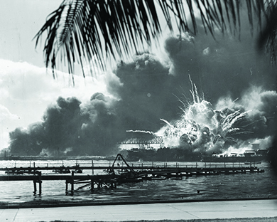 A photograph shows a long dock with the USS Shaw exploding behind it. In the far background, massive billows of smoke are visible.