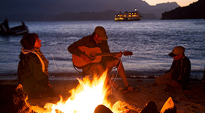 A man plays the guitar while his friends sing along around a campfire.